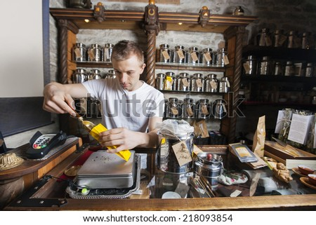 Male owner scooping ingredient into paper bag at tea store - stock photo