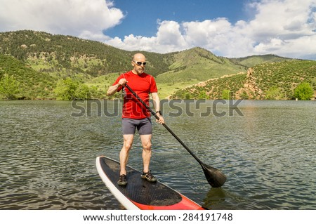 male paddler enjoying stand up paddling on a sunny summer day - Horsetooth Reservoir, Fort Collins, Colorado - stock photo