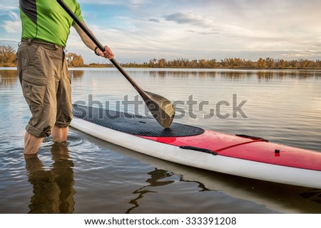 male paddler is starting  paddling workout on his stand up paddleboard on a lake in Colorado - stock photo