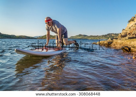 male paddler starting stand up paddling on a rocky shore of Horsetooth Reservoir, Fort Collins, Colorado, summer scenery - stock photo
