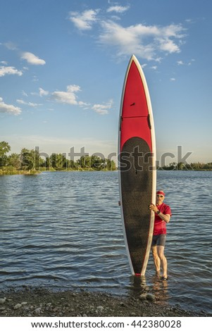 male paddler with his long stand up paddleboard on a lake shore - stock photo