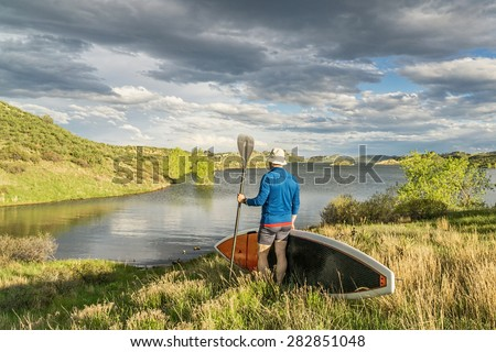 male paddler with stand up paddleboard (SUP) on a grassy shore of mountain lake - Horsetooth Reservoir near Fort Collins, Colorado - stock photo