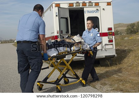 Male paramedics carrying patient on stretcher to the car - stock photo