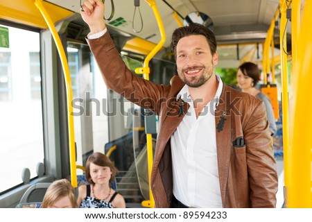 Male passenger in a bus; presumably he is heading home - stock photo