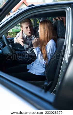 Male passenger yelling at female driver in a car - stock photo
