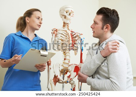 Male Patient Describing Injury To Osteopath - stock photo