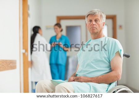 Male patient in a wheelchair looking at camera in hospital corridor