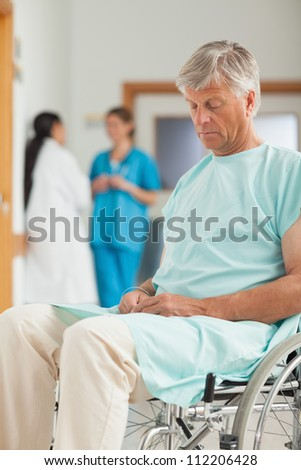 Male patient in a wheelchair next to nurses in hospital - stock photo