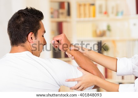 Male patient seen from behind with female physio therapist hands holding mans arm