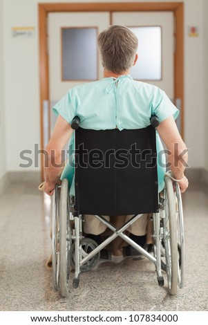 Male patient sitting in a wheelchair in hospital corridor