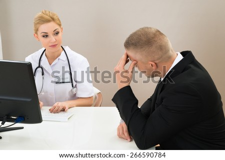 Male Patient With Young Female Doctor At Clinic - stock photo