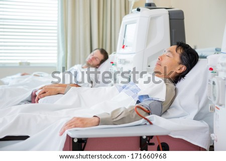 Male patients receiving renal dialysis in hospital - stock photo