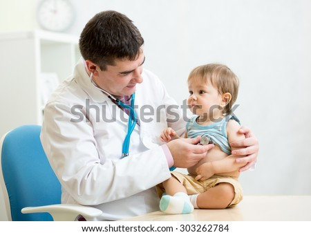 male pediatrician examining heartbeat of baby boy with stethoscope - stock photo
