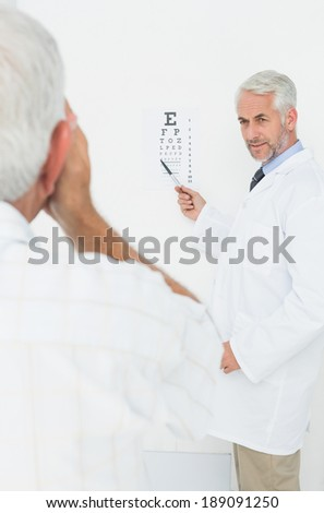 Male pediatrician ophthalmologist with senior patient pointing at eye chart in medical office - stock photo