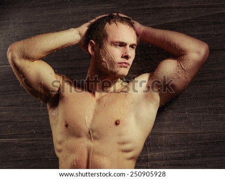 Male perfection. Closeup image of sexual gay man posing with his hands behind his head and looking away while standing under the running water