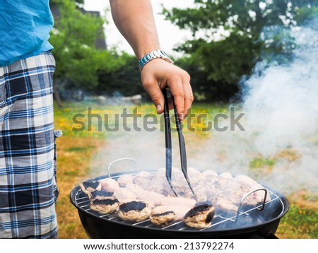 Male person with food tweezers barbequing with lot's of smoke - stock photo