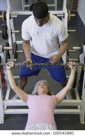 Male personal trainer with female client lifting weights - stock photo
