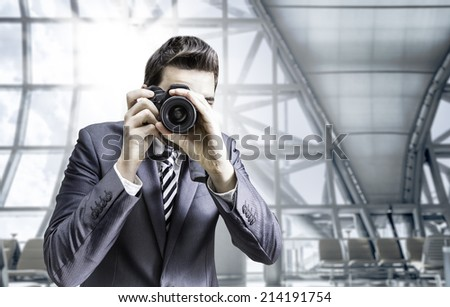 Male photographer focusing and composing an image with his professional digital SLR camera pointing the lens directly at the viewer in the airport - stock photo