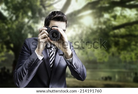 Male photographer focusing and composing an image with his professional digital SLR camera pointing the lens directly at the viewer in a park - stock photo