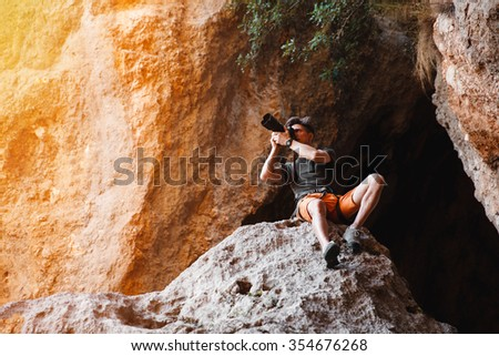 Male photographer on the cliff in the cage shooting on dslr camera. Concept of freelance working - stock image - stock photo