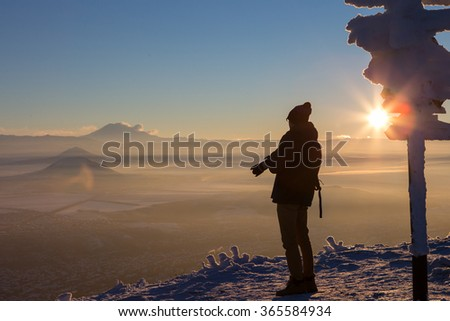 Male photographer on top of the mountain, photographed the sunset. Near the pillars direction signs. Wide angle. Silhouette.