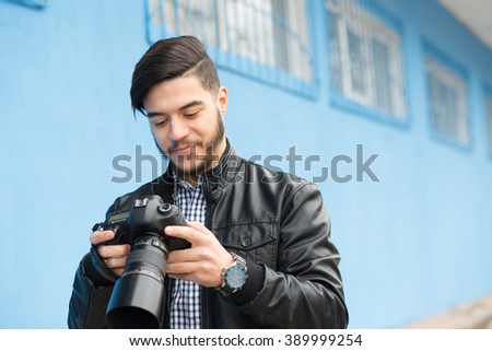 Male photographer photoshooting against a blue wall background