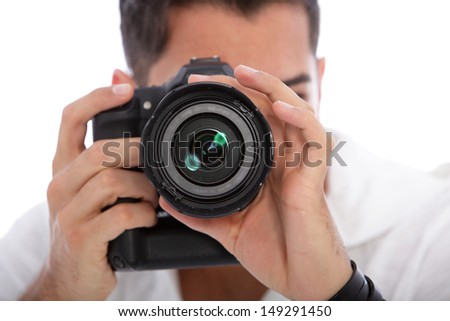 Male photographer taking a photograph focusing directly at the lens with his professional dslr camera - stock photo