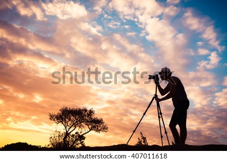 Male photographer taking photos in a beautiful nature setting.  - stock photo