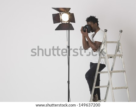 Male photographer taking photos with camera in studio - stock photo