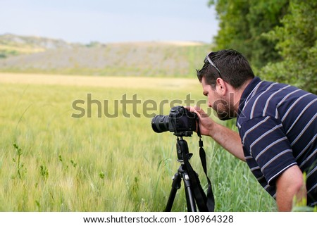 Male photographer using tripod for landscape photography - stock photo