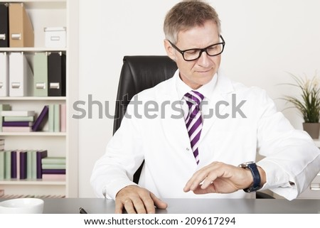 Male Physician Watching his Wrist Watch for Next Activity - stock photo