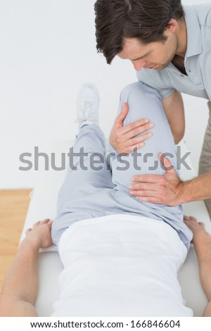 Male physiotherapist examining a young mans leg in the medical office