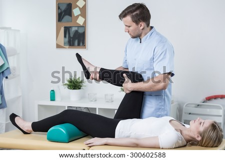Male physiotherapist exercising with patient having knee pain - stock photo