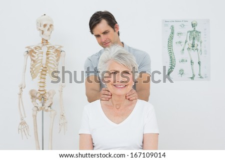 Male physiotherapist massaging a senior woman's neck in the medical office - stock photo