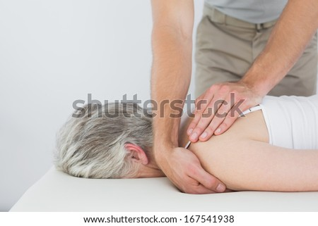 Male physiotherapist massaging a senior woman's shoulder in the medical office - stock photo