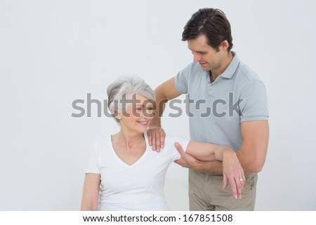 Male physiotherapist massaging a smiling senior woman's arm in the medical office - stock photo