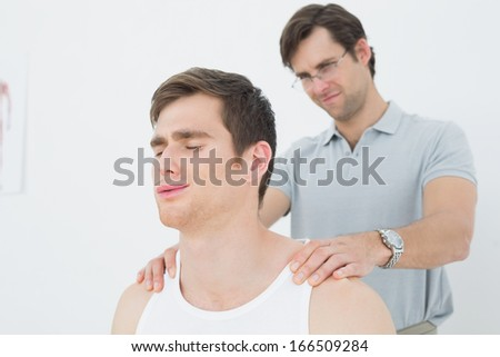 Male physiotherapist massaging a young mans shoulder in the medical office - stock photo