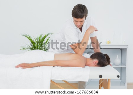 Male physiotherapist massaging woman's back in the medical office - stock photo