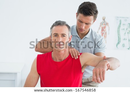 Male physiotherapist stretching a mature mans arm in the hospital - stock photo