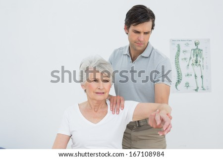 Male physiotherapist stretching a senior woman's arm in the medical office