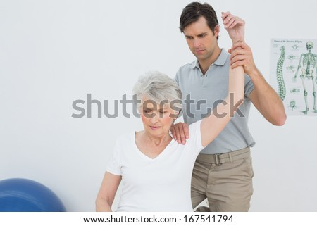 Male physiotherapist stretching a senior woman's arm in the medical office - stock photo