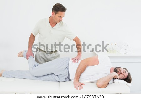 Male physiotherapist stretching man's leg in the medical office