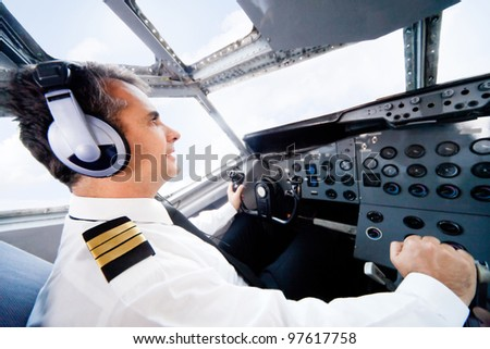 Male pilot sitting in the cabin and flying an airplane - stock photo