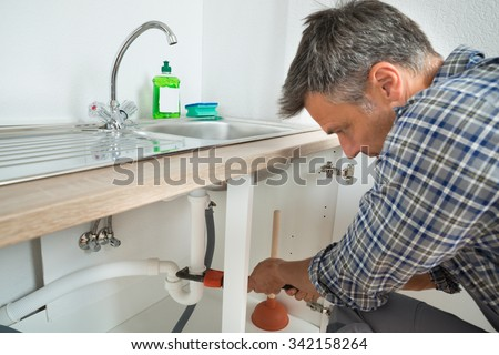 Male plumber fixing sink pipe with adjustable wrench in kitchen