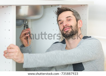 male plumber installing kitchen sink using wrench
