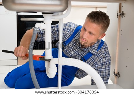 Male Plumber Repairing White Sink Pipe In Kitchen Room - stock photo