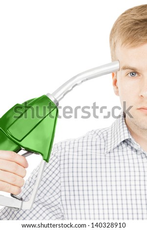 Male pointing green color fuel pump nozzle at his head - stock photo