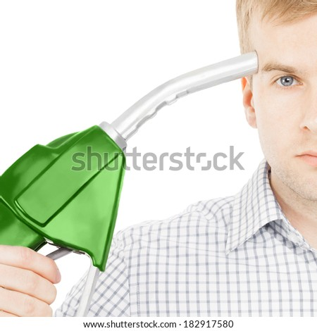 Male pointing green color fuel pump nozzle at his head - 1 to 1 ratio image - stock photo