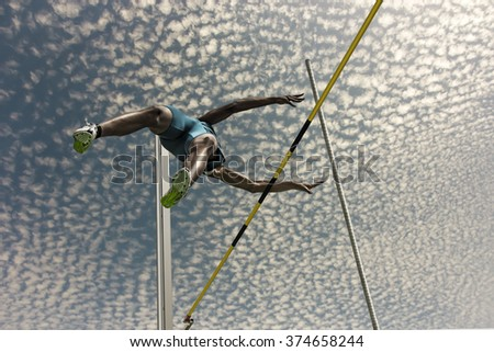 Male pole vaulter jumps  over the yellow black striped bar - stock photo