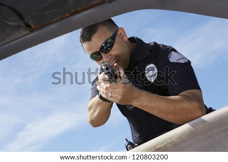 Male police officer aiming gun at broken car - stock photo